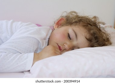 A young child fast asleep in bed.