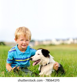 A young child in a field with his pet dog