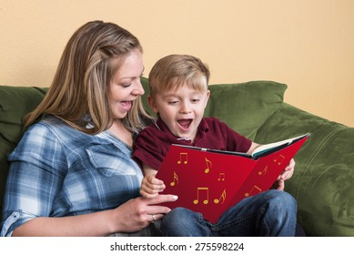 A young child gets ready to read by singing with his mother using a book based on a song.