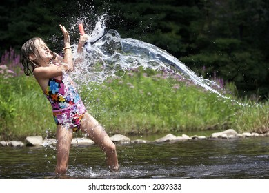 A young child getting splashed by a stream of water in knee deep water at a river, she is holding a snorkel
