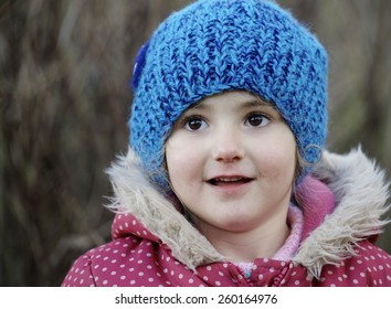 Young child, girl, with a bright blue woolly hat on. playing outdoors. She has beautiful big brown eyes and is playing in the woods.