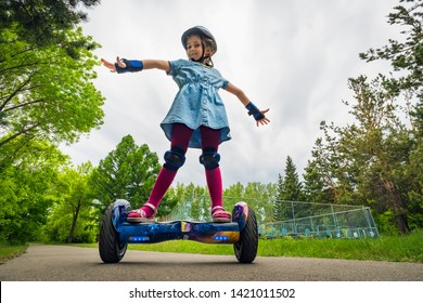 A young child girl riding in a city Park on a gyroscooter. Summer entertainment in nature. Electric scooter is a modern eco-friendly mode of transport. self-balancing scooter