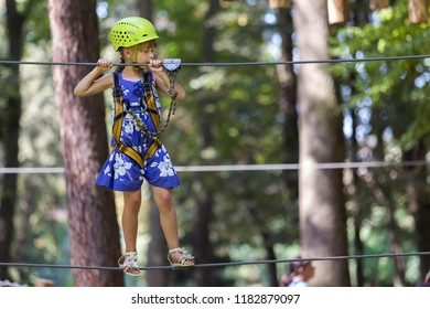 Young child girl in safety harness and helmet attached with carbine to cable moves carefully along rope way in recreation park on green foliage sunny bokeh background. Sport, game and leisure concept.