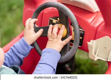 Young child with hand honking horn on steering wheel of toy car