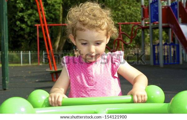 Young child having fun on a ride at the playground. The ride is green and is a see-saw and the pretty toddler is wearing a pink top. She has blonde curly hair and is holding on tight.