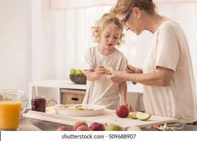 Young child helping it's grandother with baking an apple pie