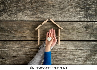 Young child and his father indicating their love for a home in a conceptual image with their hands holding a heart inside the frame of a house.