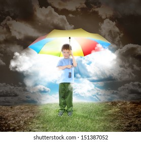 A young child is holding a rainbow umbrella with sunshine glowing out. The boy is surrounded with a dried up landscape and grass under his shoes for a home concept.