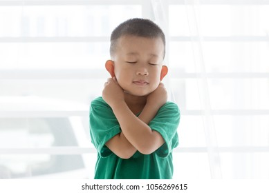 Young child at home. Playful Asian boy get punished by pulling ears.