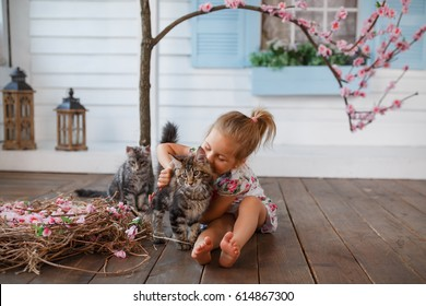 A young child hugging a small kitten, very tender moment, lots of love. Little girl with cat