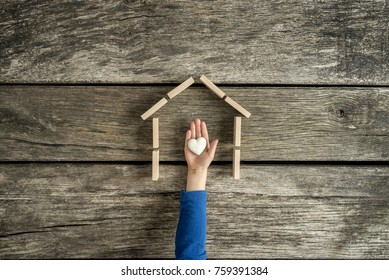 Young child indicating his love for his home in a conceptual image with his hand holding a heart inside the frame of a house.