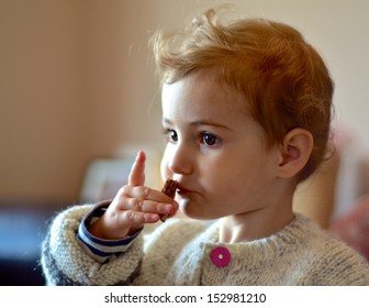 Young child indoors eating a snack.