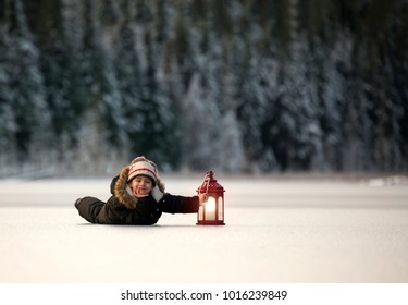 Young child laying on a frozen lake holding a retro candle lit lantern.