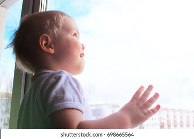 A young child looks through a window, beautiful sunlight