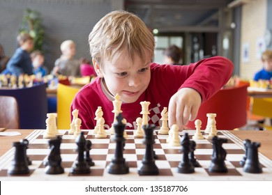 Young child making a move with a horse during a chess tournament at a school, with several other competitors in the background