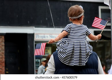 Young child on her fathers shoulder waving American Flags