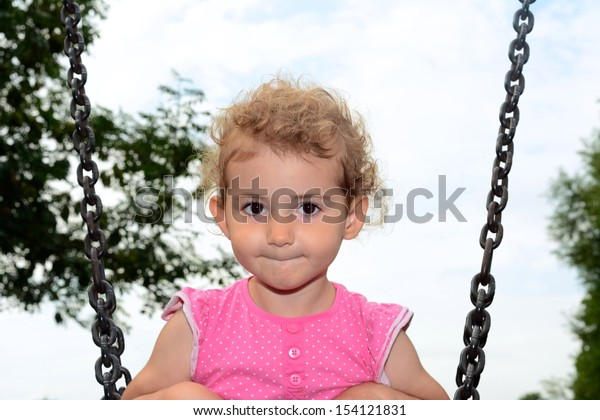 Young child on a swing at the park. Toddler girl smiling on a swing at the playground. She is wearing pink top and has blonde curly hair. Low viewpoint with white cloudy sky and trees background.