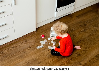 Young child play alone with pills tablets on home kitchen floor. Keep away from children reach concept. No medicine cabinet.