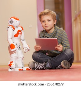 Young child playing with humanoid robot during school time