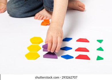 Young child playing and learning to do math with with deci pattern blocks against white background in studio