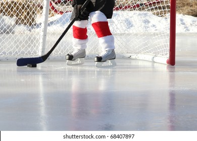 Young child playing outdoor pond ice hockey