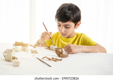 Young child plays as a paleontologist at home