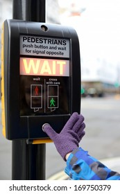 a young child pressing button at a road crossing aware of road safety focus on sign