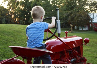 Young Child pretending to drive the red antique tractor in the field.