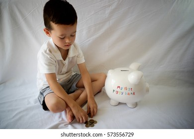 A young child putting money in his piggy bank saving money