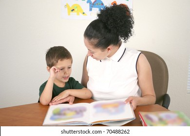 A young child reads a book with help from a teacher or tutor