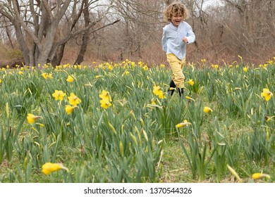A young child is running through a field of flowers in the spring. The yellow flowers match his yellow pants. He is wearing rain boats. The child is active outside in the countryside. Boy playing