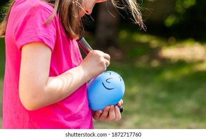 Young child, sa little girl drawing a happy smiling face on a ballon using a black marker outdoors, closeup. Children and imaginary friends, loneliness, creative arts and crafts ideas abstract concept