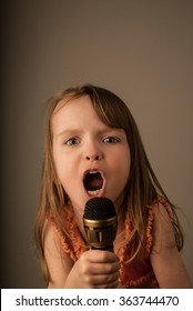 Young child singing into a handheld microphone with expressive open mouth, on plain neutral background