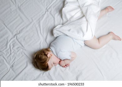 A young child sleeping with bare legs and arms and a white blanket.