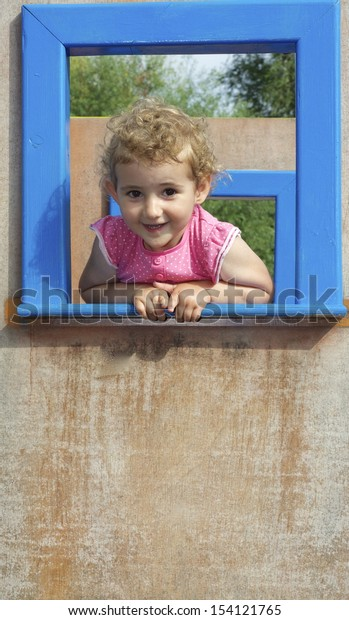 Young child smiling, framed by an open frame of blue window at the playground. The pretty blonde toddler girl is wearing a pink t-shirt. The lower part of the picture is plain wood, suitable for copy.