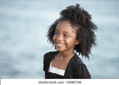 Young child smiling with water in the background