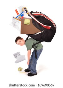A young child is standing with a large heavy school book bag on his back for a homework or stress concept on a white background.