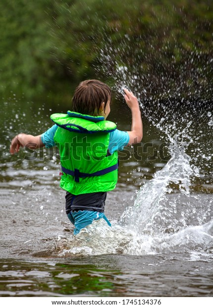 Young child standing in a rural lake wearing a life jacket making a big splash with his hand.