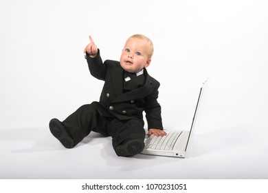 Young child in suit working on a laptop computer, isolated