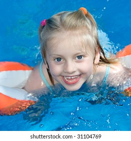 Young child is swimming in a pool