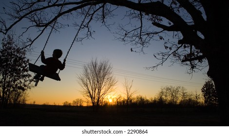 Young child swinging on swing in sunset