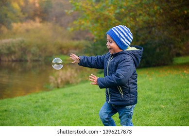 Young child trying to catch a bubble in a garden