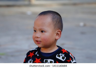 A young child in a village near the rice fields of Yunnan, China. The famous terraced rice fields of Yuanyang in Yunnan province in China. Yunnan, China - November, 2018.
