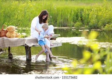 Young child walking in grass with his mother near a lake