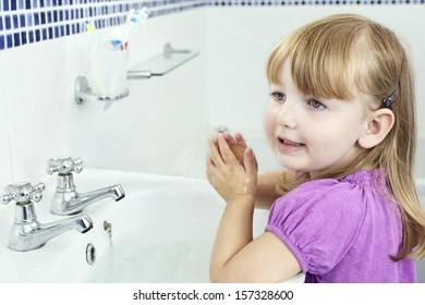 a young child washing her hands in a bathroom sink