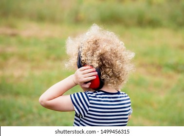 Young child wearing noise blocking headphones at outdoor concert, preventing hearing loss at young age concept.