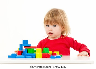 A young child wearing a red shirt plays with colorful blocks.