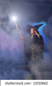 Young child in a wizard costume casting a spell.