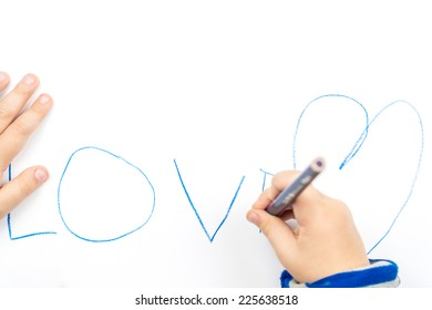 young child is writing the word love on white paper using blue pencil, two hands of a child laying on white paper with love word written on it