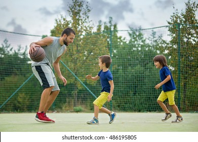 Young children, brothers and their father, playing basketball in the park
